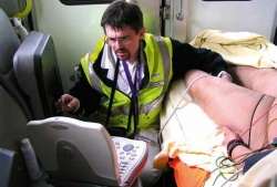 Dr Tomislav Petrovic examines a patient in an ambulance. Using a laptop-size...