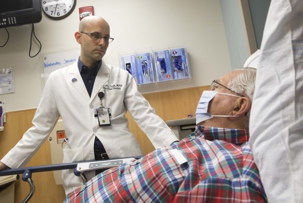 Ephraim Tsalik, M.D., Ph.D., at Duke Health assesses a patient for respiratory...