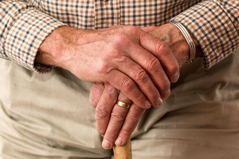 hands of an older person holding a cane