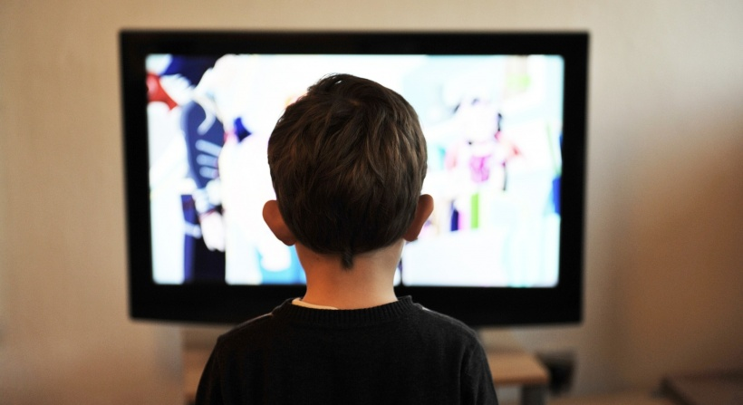 child sitting in front of tv screen