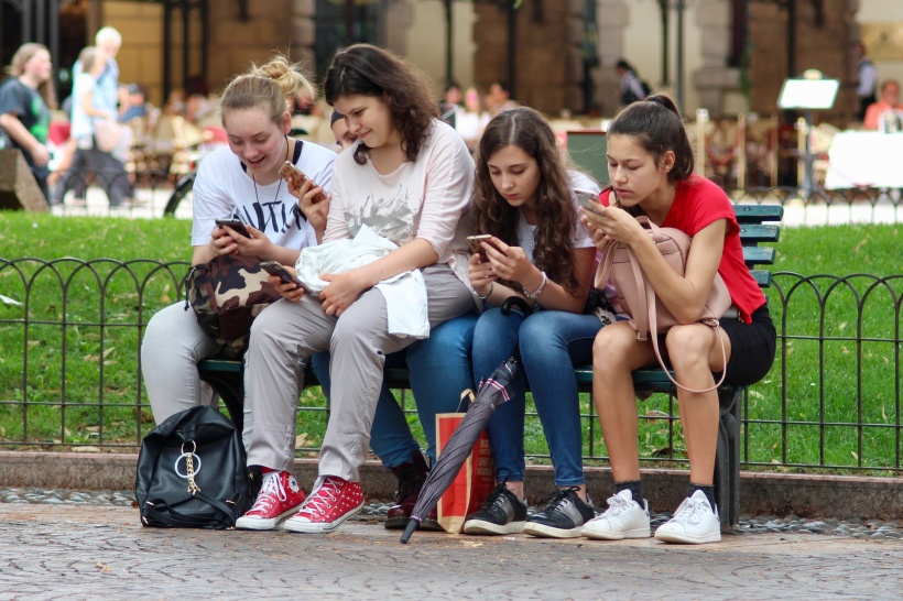 four teenaged girls sitting on a bench, using their smartphones