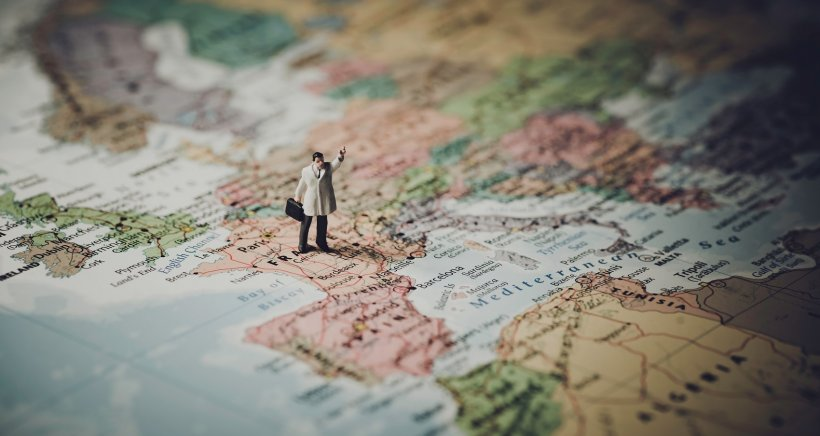 figurine standing on a map of europe, tilt-shift perspective