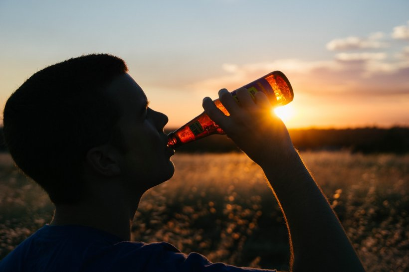 silhouette of a man drinking from a beer bottle against the sunset