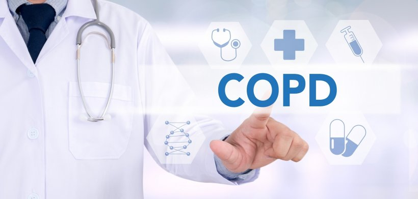man in doctors white coat pointing at virtual health symbols around the word...