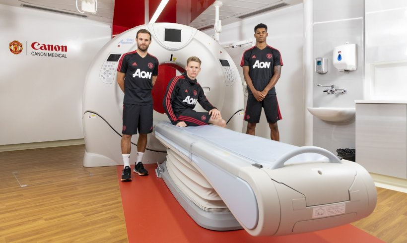 3 soccer players standing around and sitting on volume ct device