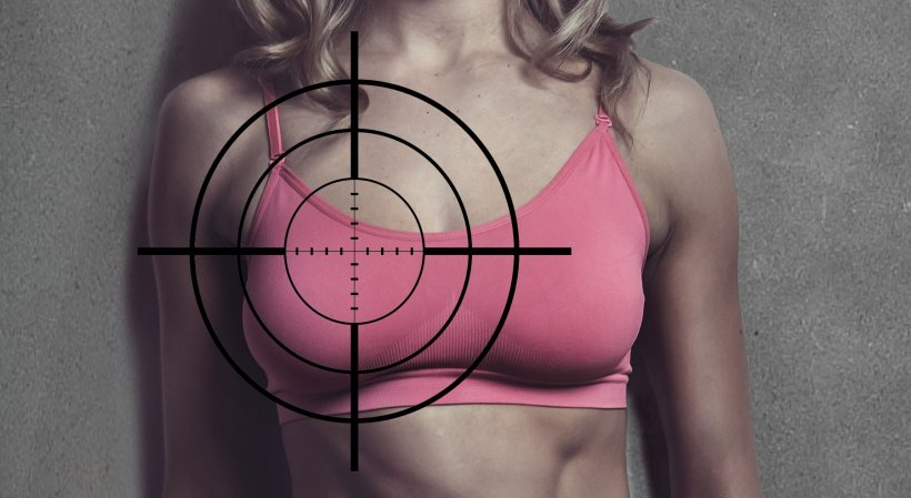 sniper crosshair on breast of woman wearing a pink sports bra