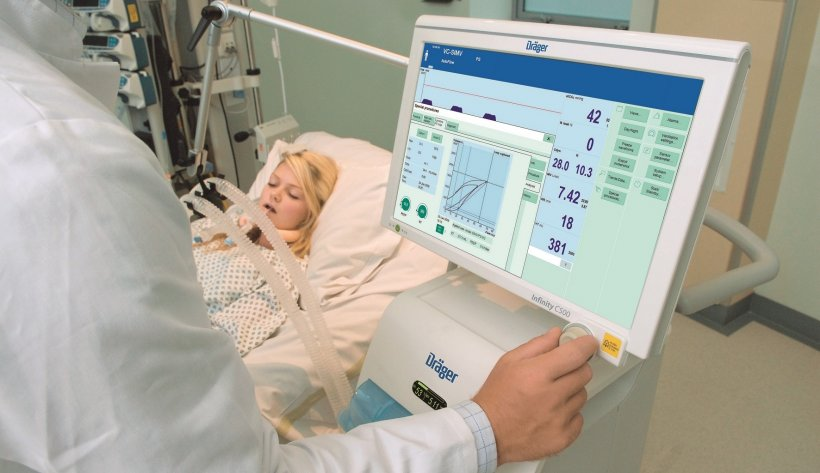 doctor operating touchscreen of a ventilation device next to a hospital patient