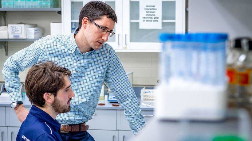 Cody Smith chats with a graduate student in his lab.