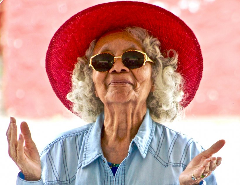 elderly woman with sunglasses and red hat