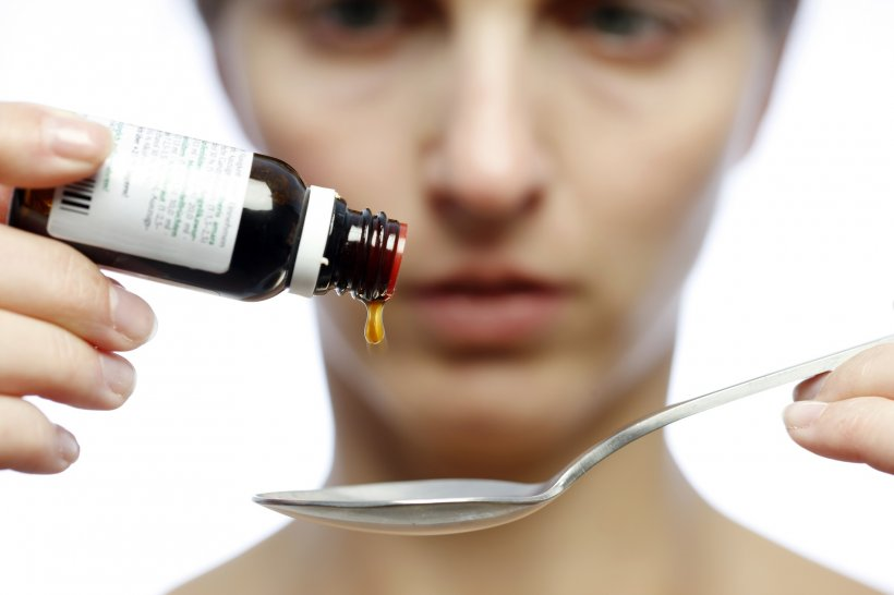 woman applying liquid medicine drops onto a spoon