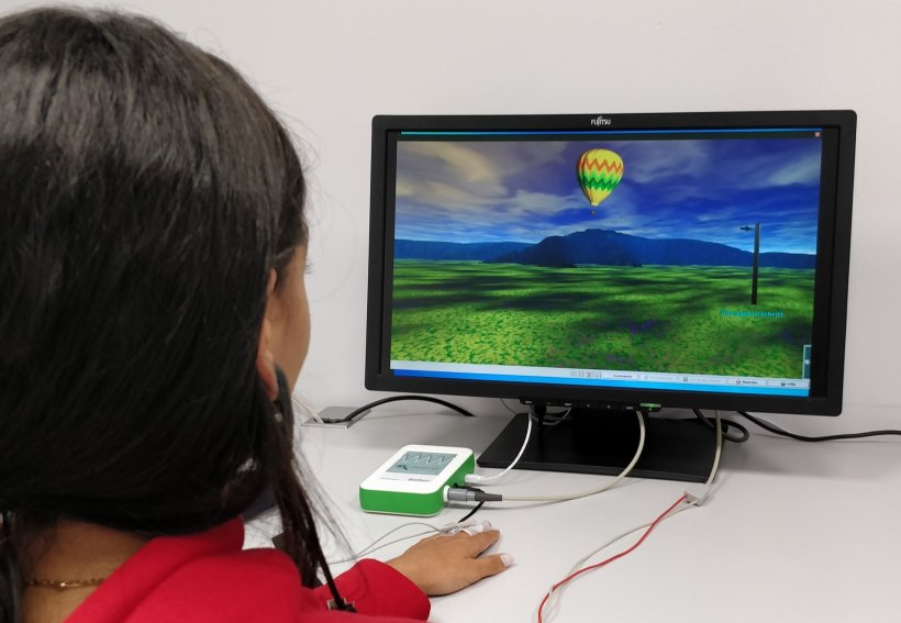 woman looking at computer monitor displaying virtual landscape with balloon