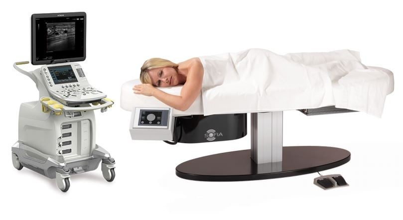 Product photo of the ultrasound system with a woman lying on the table