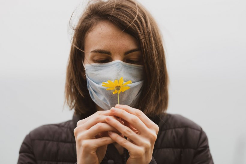 woman in black jacket with face mask sniffing yellow flower