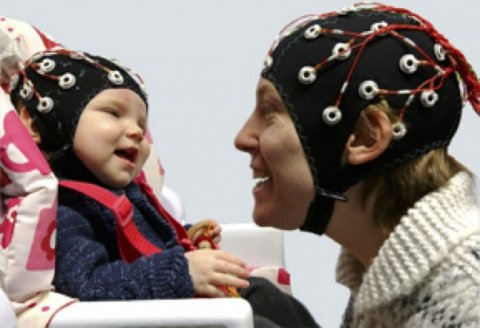 baby and adult wearing brain activity monitoring caps