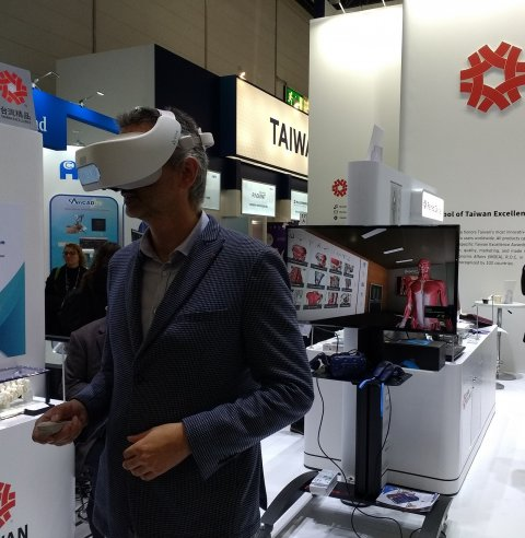 man with vr glasses exploring 3d anatomical model at medical fair