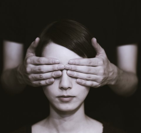 woman having her eyes covered by hands of a person behind her
