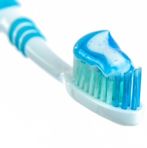 blue and white toothpaste on toothbrush