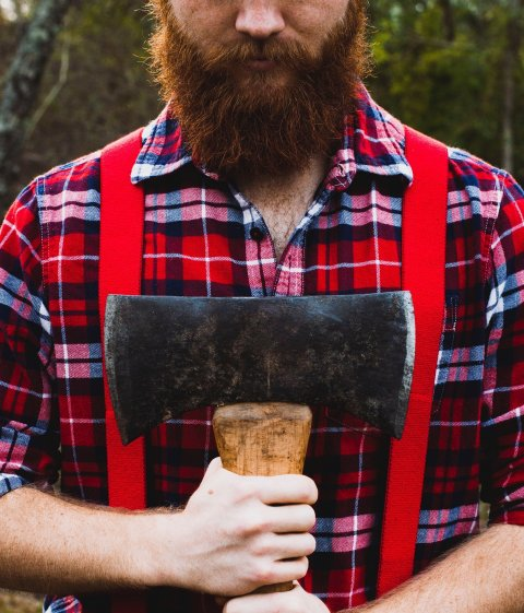 man with red beard and lumberjack shirt holding a double-bladed axe