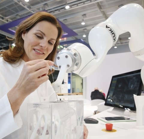 woman interacting with robotic arm