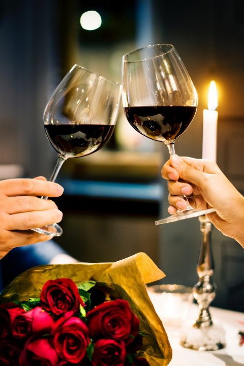two people raising their red wine glasses