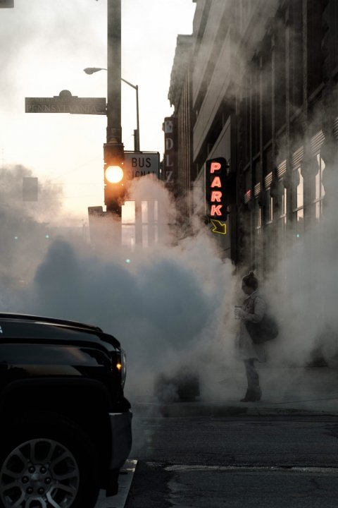 person standing on street corner with air pollution, car exhaust