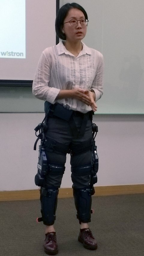 woman with robotic exoskeleton standing next to man in business suit