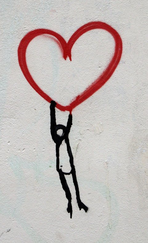 graffiti of stick figure man hanging on to red heart