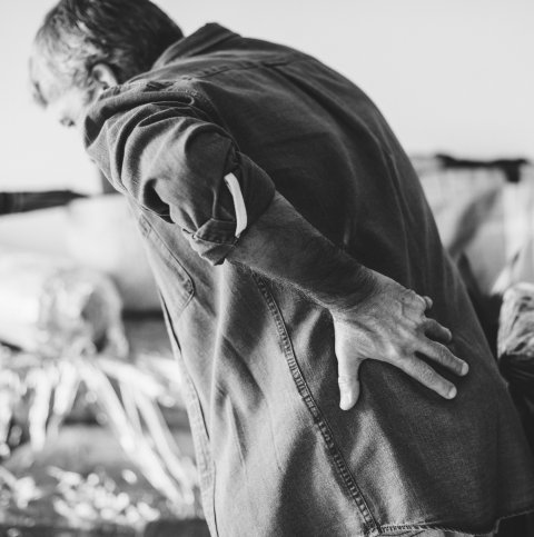 grayscale photo of man holding his back in pain