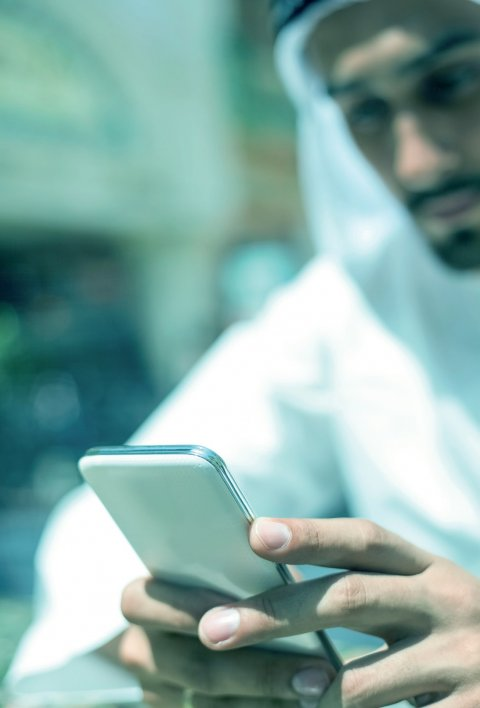out of focus photo of sheikh in dubai looking at a smartphone