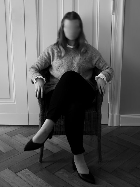woman with blurry face sitting in a chair