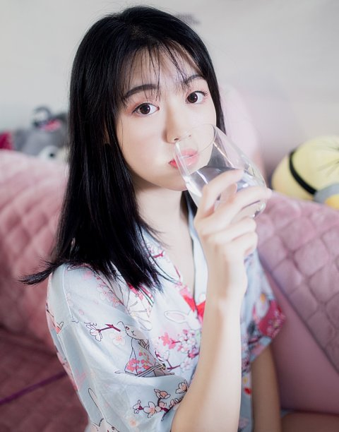 asian woman drinking water from a glass