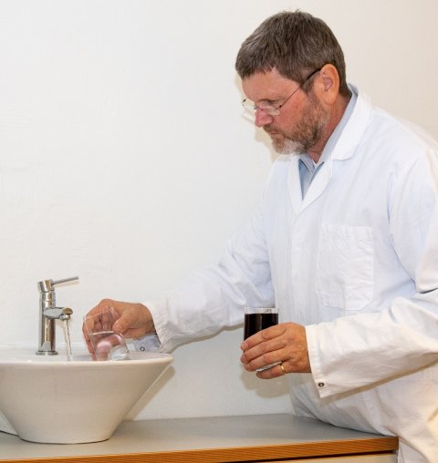 man in white lab coat using a water tap