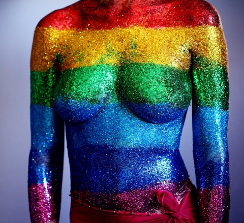female body covered in rainbow-colored glitter stripes