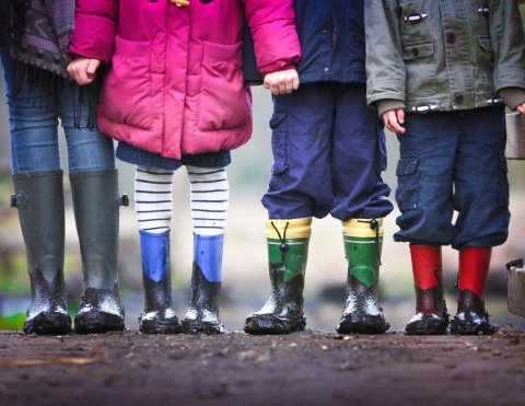 four children wearing muddy boots