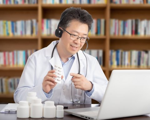 asian doctor sitting in front of laptop holding pill bottle