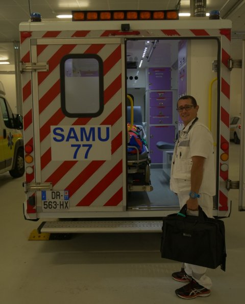 medic standing next to ambulance holding a black suitcase