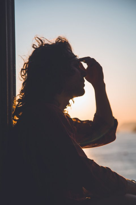 silhouette of woman holding her forehead from headache