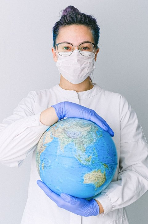 woman in white coat wearing face mask holding a globe