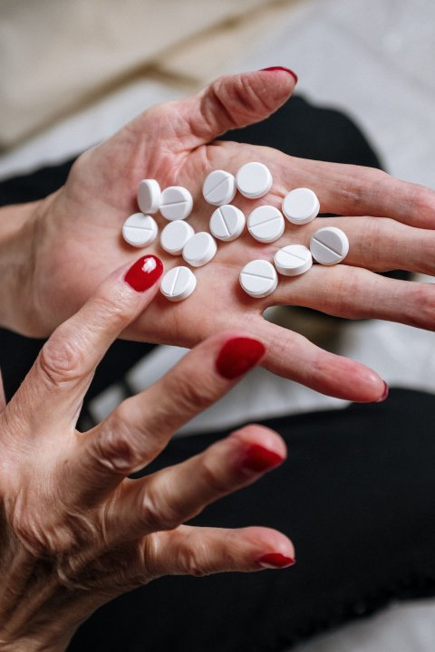 woman with red fingernails holding white pills in her hand