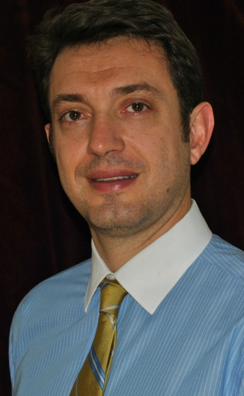 Dr Marcio Sommer Bittencourt wears a blue shirt and a golden tie.
