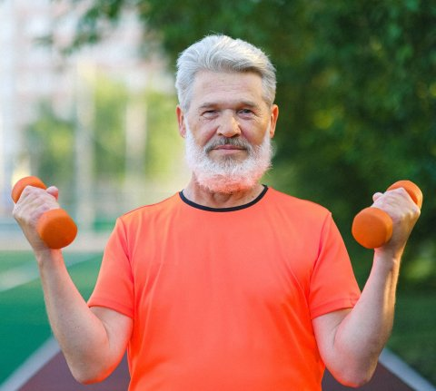 older man in orange shirt lifting small weights