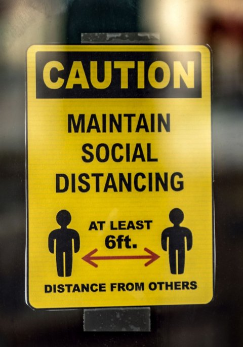 yellow and black social distancing sign