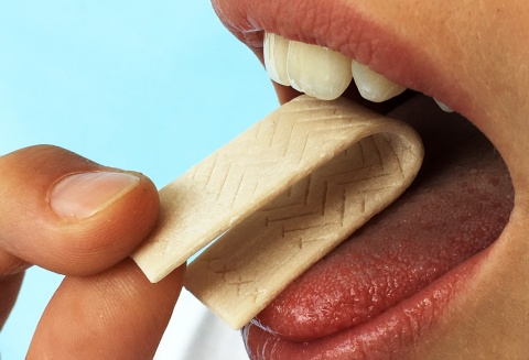 closeup of a person putting chewing gum in mouth