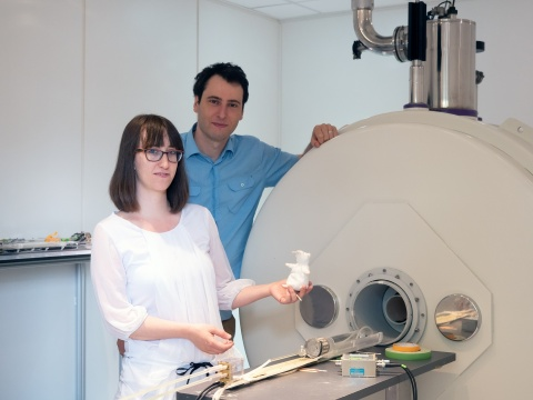 scientists standing next to a mri scanner for small animals