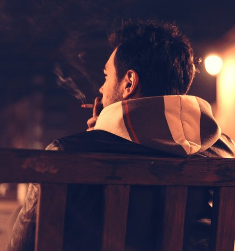 smoking man sitting on a bench
